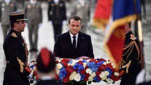 Frankrikes president Emmanuel Macron lägger en blomsterkrans på den okände soldatens grav under Triumfbågen.