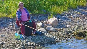Kvinna sitter och fiskar på stranden.