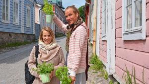 Man och kvinna står på en kullerstensgata med nyinköpta örter.