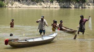 Sju personer står i en flod och det finns två båtar.