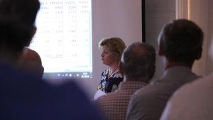En kvinna med trumpen står framför en videoduk och presenterar dystra ekonomiska siffror.