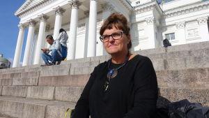 Kvinna sitter i Senatstorgets trappor i solskenet