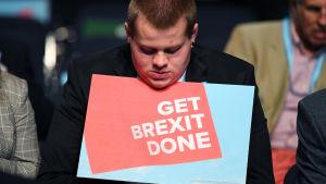 "En ung man ses hålla i en skylt med orden ""Get brexit done"" (fixa brexit) ."