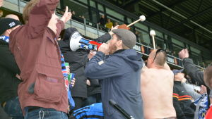 Fotbollssupportrar med megafon och trumpinnar i händerna hejar på sitt lag.