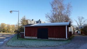 En röd ekonomibyggnad framför en större byggnad.