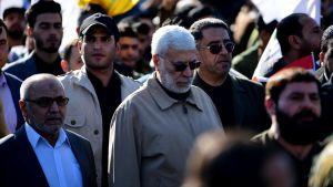 En klunga människor i en folksamling. I mitten en äldre man med grått hår, grått skägg, solglasögon och en beige jacka.