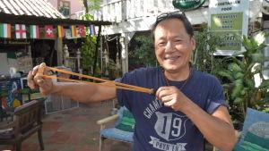 Liksom många Lopburibor har Thitinan Techawongtham alltid en slangbössa nära till hands. En del apor har slutat att bli skrämda, men för det mesta fyller slangbössorna sitt syfte. Techawongtham håller i en slangbössa och ser glad ut.
