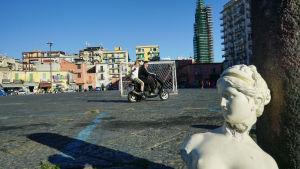 Kuva kaupunkimaisemasta, jossa edustalla näkyy valkoinen patsas, taustalla kaksi ihmistä ajaa vespalla.