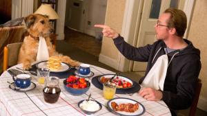 Mies ja koira istuvat ruokapöydässä.