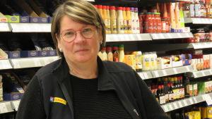 En kvinna med glasögon, kort hår, klädd i svart fleecejacka. Hon står inne i en butik. Bakom hylla med kryddor och salladsdressingar och majonnäser.