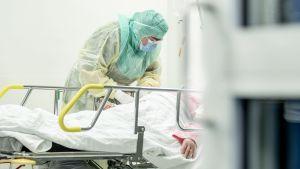 Vårdare i skyddsutrustning tar hand om en patient som ligger i en sjukhussäng.