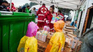 Röda korsets personal delar ut förnödenheter i ett tält.
