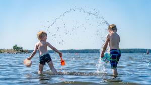 Barn leker i vattnet vid en badstrand i Nordsjö i Helsingfors den 25 juni 2020.