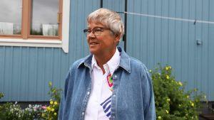 En äldre kvinna står framför ett ljusblått hus.