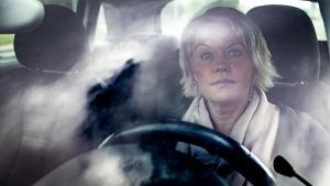 Kvinna sitter bakom ratten i sin bil och ser in i kameran som befinner sig på andra sidan vindrutan.