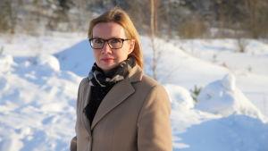 Kvinna i glasögon och vinterkappa i ett landskap med snö och små träd bakom sig. Kati Arell skulle ha önskat sig att Konkurrens- och konsumentverket skulle ha drivit en grupptalan mot Fi-Nergy.