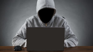 Anonym person framför en laptop