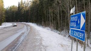 En vinterslaskig väg, i förgrunden syns en blå vägskylt med texten Borgå 6 och Sondby 13.
