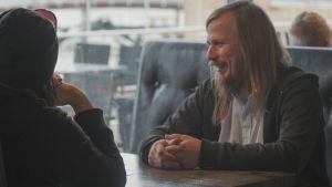 Musikern Ville Karttunen sitter vid ett restaurangbord intill ett stort fönster.