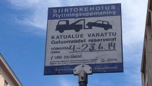En skylt vid Petersgatan i södra Helsingfors uppmanar bilisterna att flytta på sina fordon.