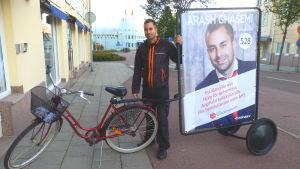 Socialdemokraternas kandidat Arash Ghasemi saknar åländsk hembygdsrätt och kan därför kandidera endast i stadsfullmäktigevalet i Mariehamn. Kampanjfordonet är cykeln.