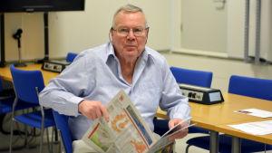 Ralf Friberg sitter med en tidning i handen.