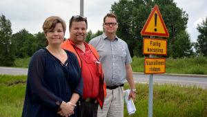 """Mia Skog, Ulf Österman och Jan Gröndahl står vid en skylt där det står """"farlig korsning""""."""