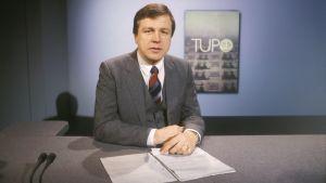Yleisradion TV-uutiset. Toimittaja Arvi Lind lukemassa uutisia tv-studiossa, taustalla TUPO-aiheinen dia (tv-grafiikka, taustakuva). Uutisankkuri työssä. Uutistoimittaja juontaa tv-lähetystä. Uutisstudio. Yleisradion ohjelmat.