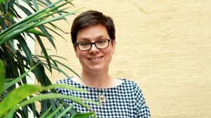 Bild på korthårig brunett med glasögon mot gul vägg, gröna palmblad i förgrunden.