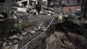 En kvinna med sitt barn ser över förödelsen nära Costa Ricas huvudstad San Jose som drabbades av häftiga regn och jordskred