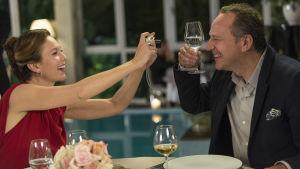 Anne (Diane Lane) sitter vid ett bord och fotograferar Jacques (Arnaud Viard) som skålar med henne.