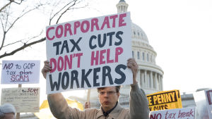 """""""Sänkta företagsskatter hjälper inte arbetarna"""" står det på den här demonstrantens plakat. Han demonstrerade mot republikanernas skattereform utanför Kapitolium i torsdags."""