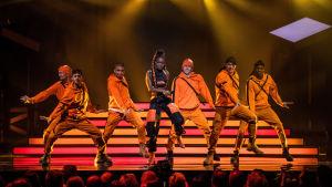 Kvinna omgiven av manliga dansare i orange