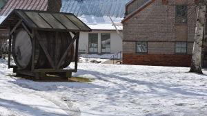 En gammal öltunna på en snöig gård.