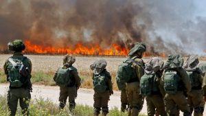 Israeliska soldater står intill en brand på ett vetefält nära en kibbutz intill Gazaremsan.