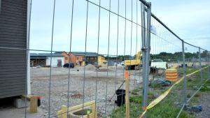Byggarbetsplats på grusplan bakom stängsel. Bostadshus i bakgrunden.