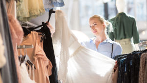 Ljushårig kvinna synar en vit klänning i en klädffär