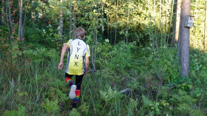 En pojke springer bort från kameran i en grön skog. Han har på sig en vit-gul träningsskjorta som det står Lynx på och randiga färggranna strumpor.