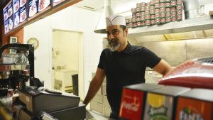 En man står framför kassan i en pizzeria i Ekenäs