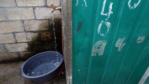 Vatten samlas upp i fat från kommunal källa i Cape Town.