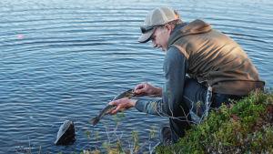 Nuori mies istuu järvenrannalla ja irrottaa koukkua kalasta.