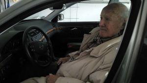 En äldre man sitter i förarsätet på sin bil.