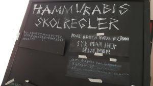 svart liten griffletavla med vit text. Det står Hammurabis lagar på den