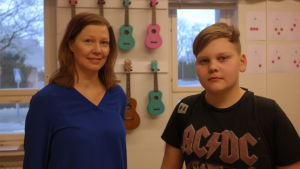 Musiklärare Micaela Sundström och hennes elev Alexander Helsender står framför en vägg med färgglada ukulelen