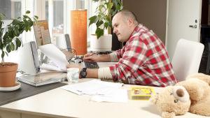 En medelålders man jobbar hemifrån