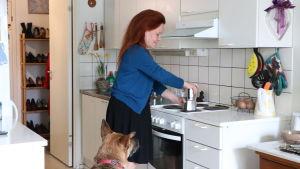 Lena Bengtson står i sitt kök och lagar kaffe. Hennes hund sitter bredvid henne på golvet och tittar på.