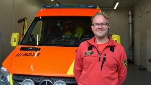 Akutvårdare ler framför en ambulans