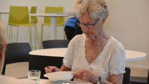 En äldre dam sitter vid bordet och skrapar tallriken.