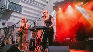 Vaaleahiuksinen nainen aurinkolasit pääsään soittaa kitaraa lavalla, toinen vaaleahiuksinen nainen soittaa syntetisaattoria. Taustalla on savua ja punaista valoa.