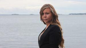 Erica Helin tittat allvarsamt i kameran. Svart klädsel, havet i bakgrunden.